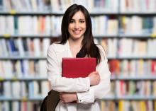 Bücherrei, Mädchen steht mit rotem Buch vor einem Buchregal